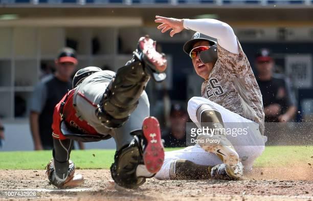Christian Villanueva of the San Diego Padres scores ahead of the tag of John Ryan Murphy of the Arizona Diamondbacks during the eighth inning of a...