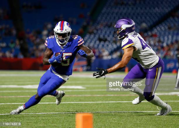 Christian Wade of the Buffalo Bills runs the ball as Nathan Meadors of the Minnesota Vikings looks to make a tackle during the second half of a...