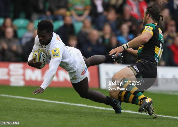 Christian Wade of Wasps dives over for their first try despite being held by Ben Foden during the Aviva Premiership match between Northampton Saints...