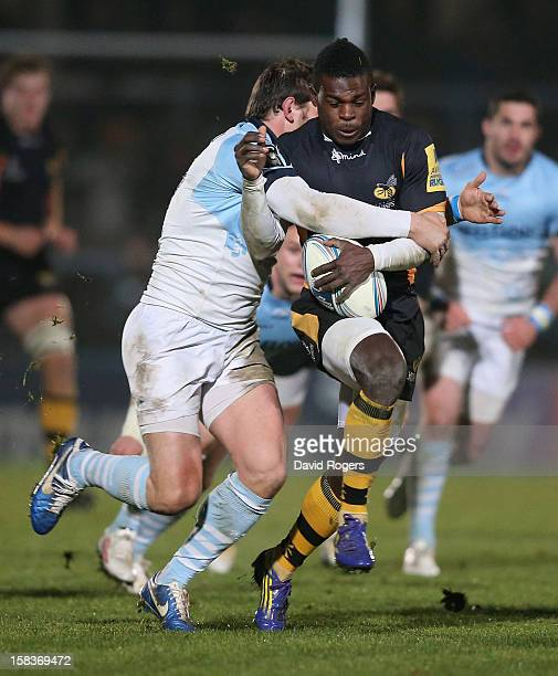 Christian Wade of Wasps is tackled by Cedric Heymans during the Amlin Challenge Cup match between London Wasps and Bayonne at Adams Park on December...