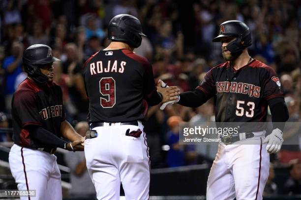 Christian Walker of the Arizona Diamondbacks is congratulated by Josh Rojas and Domingo Leyba after hitting a grand slam in the seventh inning of the...