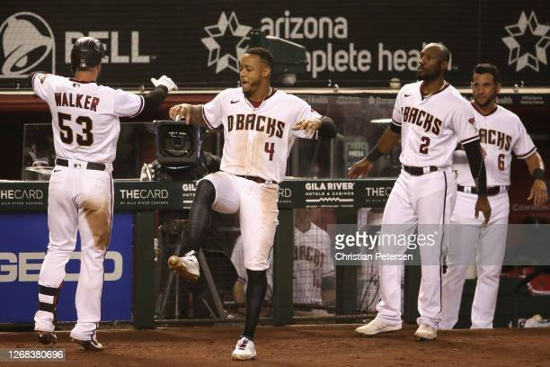 Christian Walker of the Arizona Diamondbacks is congratulated by Ketel Marte, Starling Marte and David Peralta after a solo home run against the...