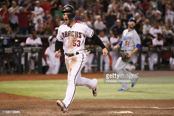 Christian Walker of the Arizona Diamondbacks reacts as he scores a run off relief pitcher Dylan Floro of the Los Angeles Dodgers during the eighth...