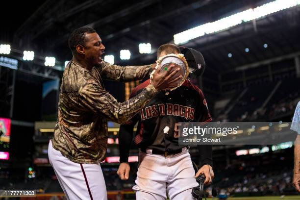 Christian Walker of the Arizona Diamondbacks receives a pie in his face from Adam Jones after the MLB game against the San Diego Padres at Chase...