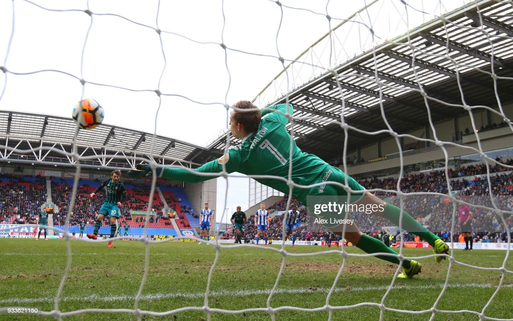 Christian Walton of Wigan Athletic (1) saves a penalty from Manolo Gabbiadini of Southamptonduring The Emirates FA Cup Quarter Final match between Wigan Athletic and Southampton at DW Stadium on March 18, 2018 in Wigan, England.
