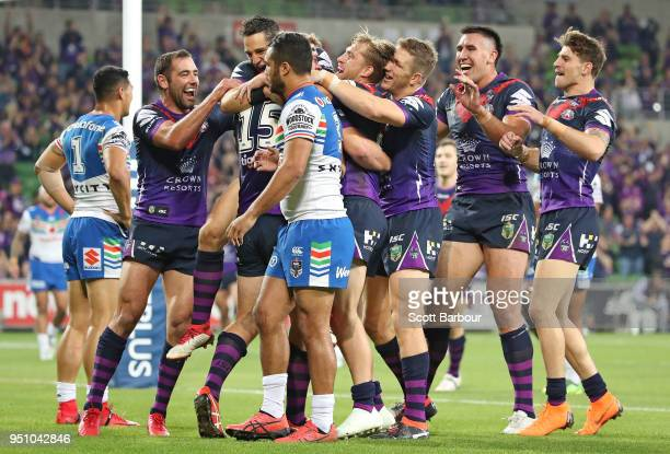 Christian Welch of the Melbourne Storm is congratulated by Billy Slater of the Melbourne Storm and his teammates after scoring a try as Peta Hiku of...