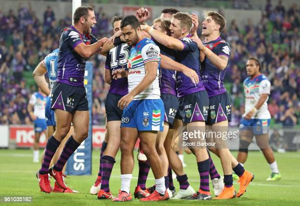 Christian Welch of the Melbourne Storm is congratulated by Billy Slater Cameron Smith and his teammates after scoring a try as Peta Hiku of the...