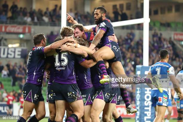 Christian Welch of the Melbourne Storm is congratulated by Josh AddoCarr Cameron Smith and his teammates after scoring a try as Peta Hiku of the...