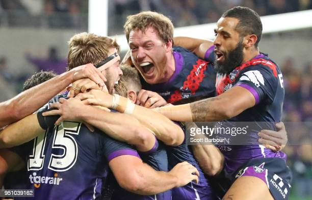 Christian Welch of the Melbourne Storm is congratulated by Josh AddoCarr Tim Glasby and his teammates after scoring a try during the round eight NRL...