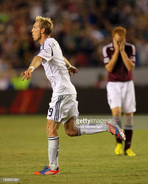 Christian Wilhelmsson of the Los Angeles Galaxy celebrates his goal in the second half as Jeff Larentowicz of the Colorado Rapids reacts dejectedly...