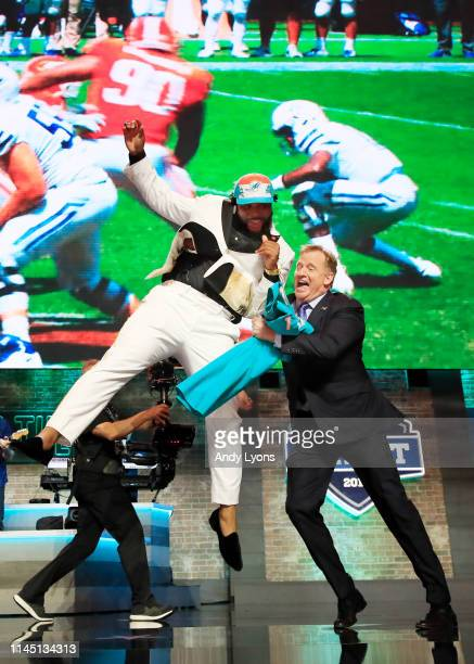 Christian Wilkins of Clemson celebrates with NFL Commissioner Roger Goodell after being chosen overall by the Miami Dolphins during the first round...