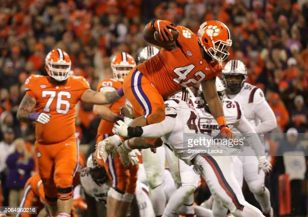 Christian Wilkins of the Clemson Tigers jumps over Sherrod Greene of the South Carolina Gamecocks to score a touchdown during their game at Clemson...