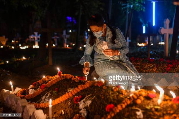 Christian woman lights candles by the grave of a relative during the All Soul's Day at a graveyard in Dhaka.