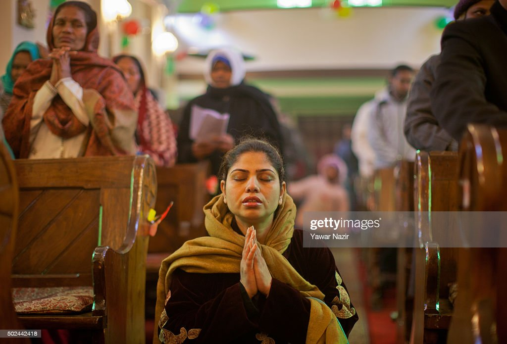 A Christian Woman Prays In The Holy Family Catholic Church During Christmas Mass On December