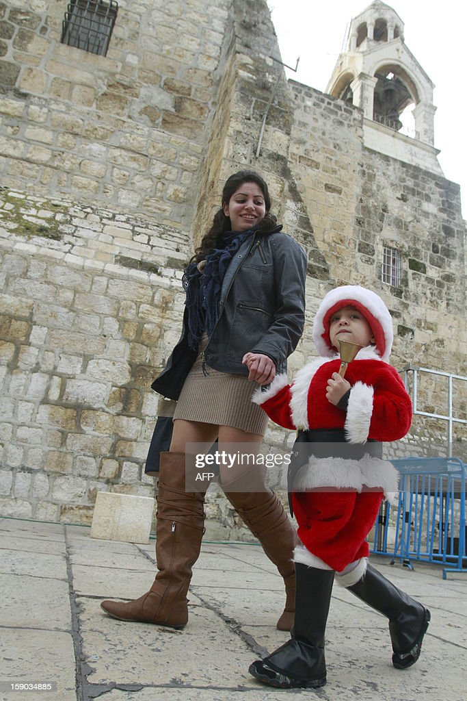 A Christian woman walks with her son dressed up as Santa Claus as they arrive outside the Church of the Nativity, the traditional birthplace of Jesus Christ, in the West Bank city of Bethlehem on January 6, 2013, as the Orthodox Church which uses the old Julian calendar celebrate Christmas eve, which Christmas falls 13 days after the more widespread Gregorian calendar (December 25) .