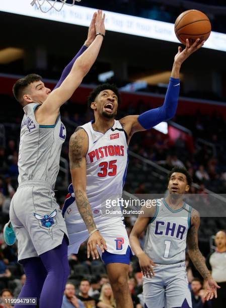 Christian Wood of the Detroit Pistons gets a shot off against Willy Hernangomez of the Charlotte Hornets during the second half at Little Caesars...