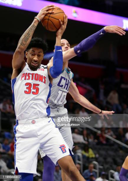 Christian Wood of the Detroit Pistons grabs a rebound in front of Caleb Martin of the Charlotte Hornets during the first half at Little Caesars Arena...