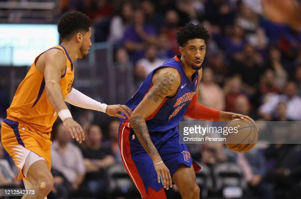 Christian Wood of the Detroit Pistons handles the ball against Devin Booker of the Phoenix Suns during the first half of the NBA game at Talking...