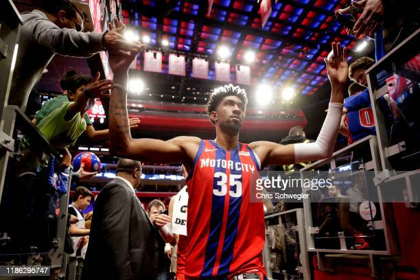 Christian Wood of the Detroit Pistons hifives fans after the game against the San Antonio Spurs on December 1 2019 at Little Caesars Arena in Detroit...