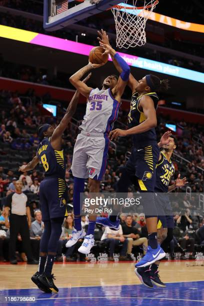 Christian Wood of the Detroit Pistons shoots between Justin Holiday and Myles Turner of the Indiana Pacers in the second quarter at Little Caesars...