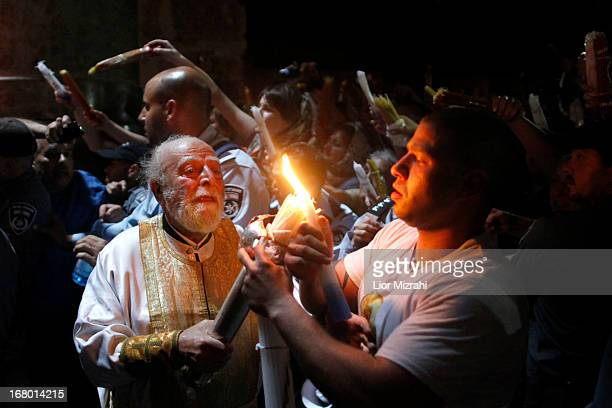Christian worshipers light candles lit from a flame that emerged from the tomb believed to be of Jesus Christ as they take part in the ceremony of...