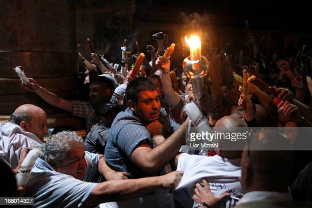 Christian worshipers struggle to light candles lit from a flame that emerged from the tomb believed to be of Jesus Christ as they take part in the...
