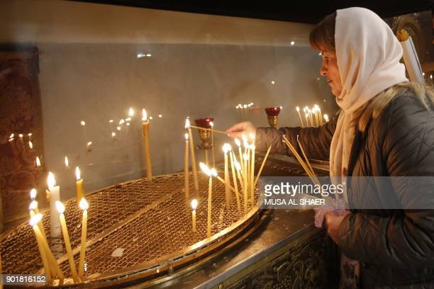 A Christian worshipper lights a candle at the church of the nativity ahead of the arrival of Jerusalem's Greek Orthodox patriarch Theophilos III in...