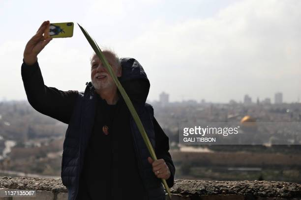 A Christian worshipper photographs himself with his smartphone as he takes part in the traditional Palm Sunday procession from the Mount of Olives to...