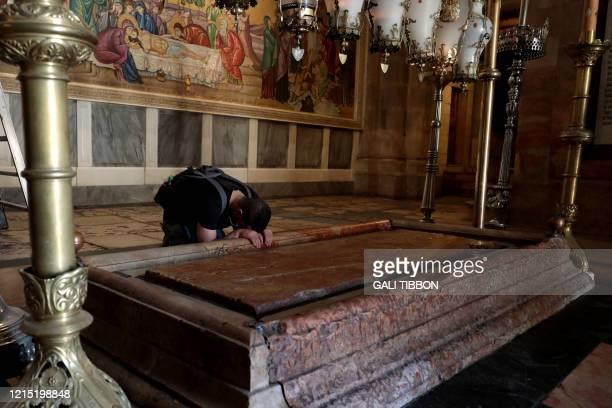 Christian worshipper prays by the Stone of the Unction in the Church of the Holy Sepulchre, in the old city of Jerusalem on May 26 as the church...