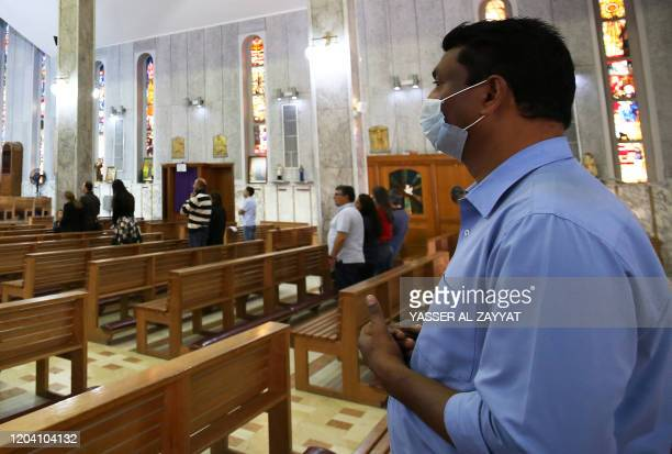 A Christian worshipper prays while wearing a protective mask at the Holy Family Cathedral in Kuwait City on February 29 2020 Saudi Arabia barred...