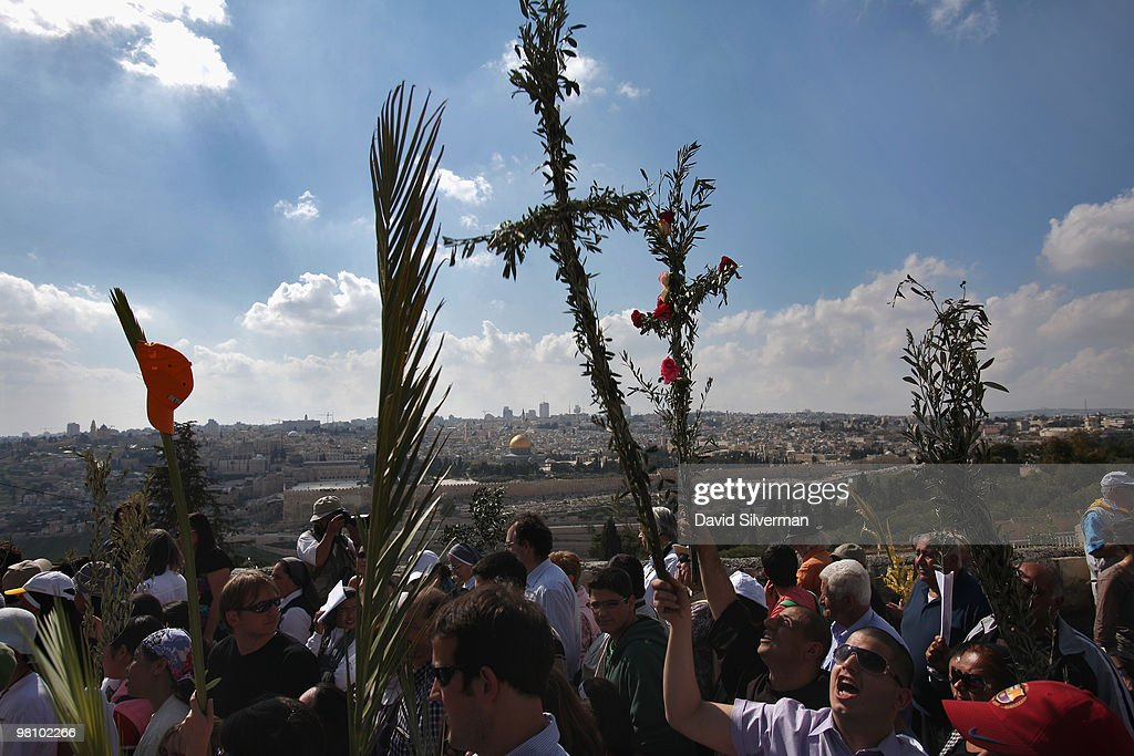 Christian worshippers and pilgrims carry palm leaves and crucifixes made of olive branches as they walk down the Mount of Olives to the Old City during the traditional Palm Sunday procession on March 28, 2010 in Jerusalem, Israel. Palm Sunday, which marks the start of Holy Week, is a landmark in the Christian calendar, marking the triumphant return of Jesus to Jerusalem the week before his death when a cheering crowd greeted him waving palm leaves.