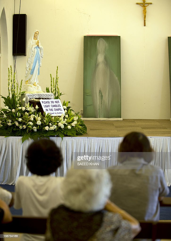 Christian worshippers pray in front of a window panel, which has an image resembling the Virgin Mary, at the Church of Our Lady of Lourdes, at the port town of Klang, on the outskirts of Kuala Lumpur on November 20, 2012. The window pane at a Malaysian hospital which has an image resembling the Virgin Mary has been moved to the church after it attracted large number of worshippers. AFP PHOTO / Saeed KHAN