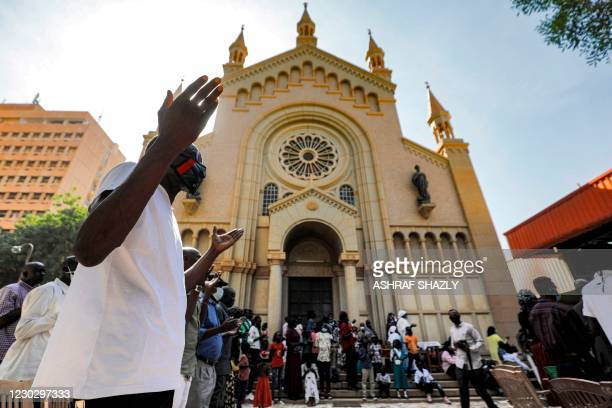Christian worshippers pray outside during Christmas morning mass at St Matthew's Roman Catholic Cathedral in Sudan's capital Khartoum on December 25,...