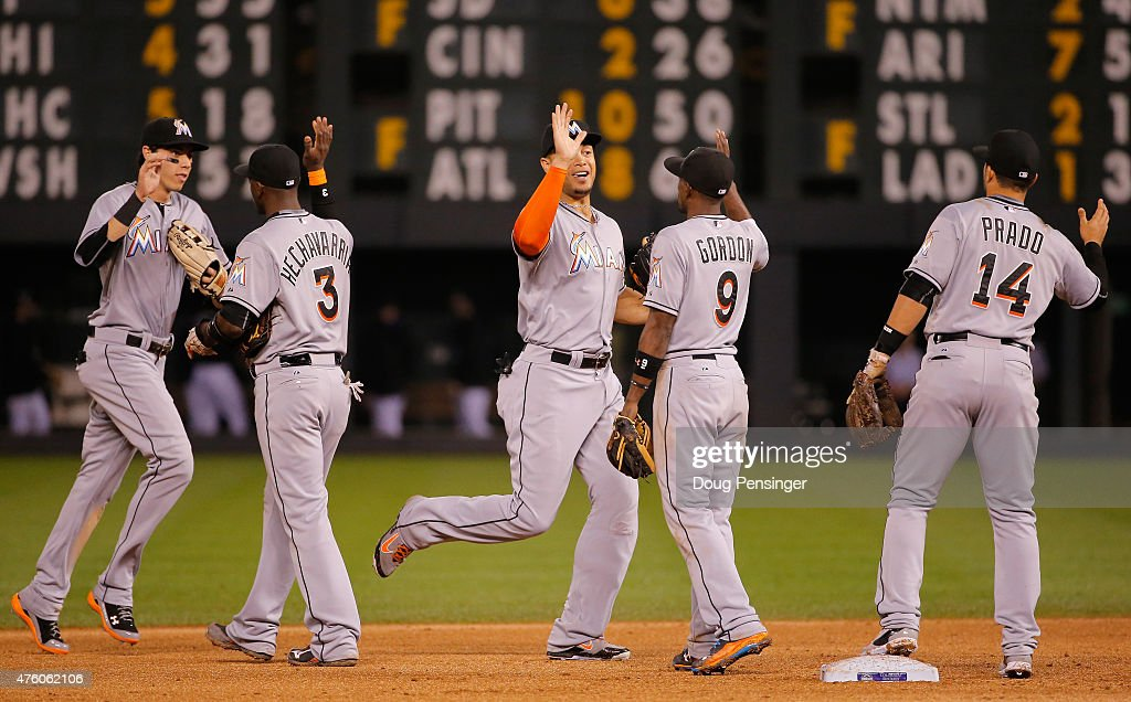 Christian Yelich #21, Adeiny Hechavarria #3, Giancarlo Stanton #27, Dee Gordon #9 and Martin Prado #14 of the Miami Marlins celebrate their 6-2 victory over the Colorado Rockies at Coors Field on June 5, 2015 in Denver, Colorado.