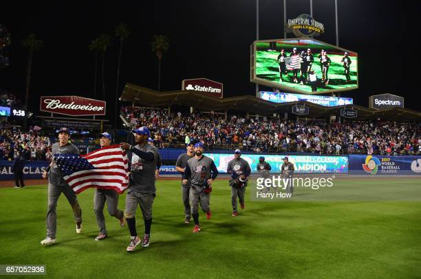 Christian Yelich Giancarlo Stanton and Adam Jones of team United States celebrate with the American Flag on the field after their 80 win over team...