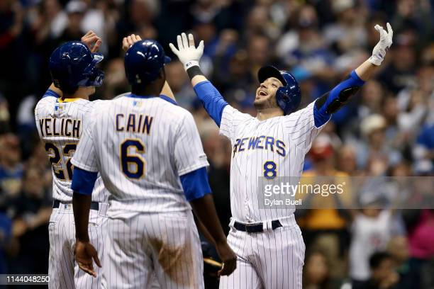 Christian Yelich, Lorenzo Cain, and Ryan Braun of the Milwaukee Brewers celebrate after Braun hit a home run in the seventh inning against the Los...
