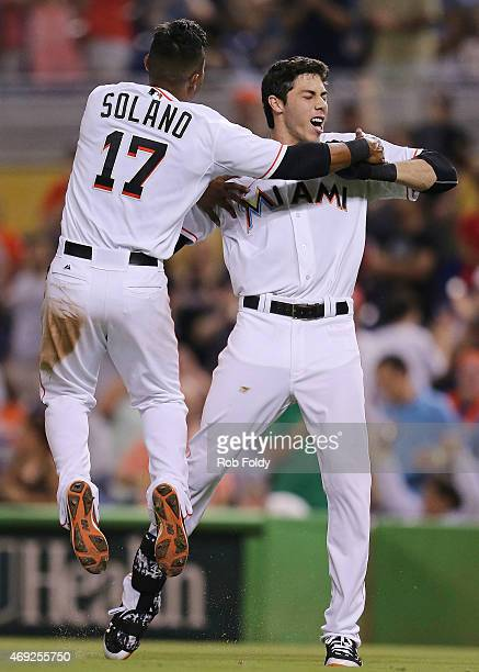 Christian Yelich of the Miami Marlins celebrates with Donovan Solano after hitting a gamewinning RBI single in the 10th inning against the Tampa Bay...