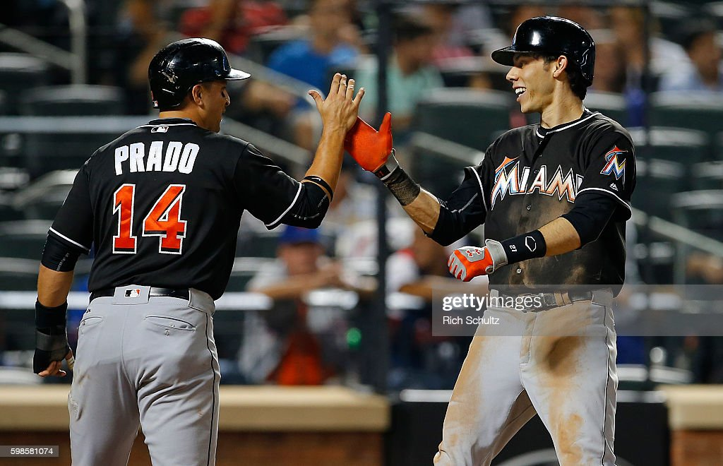 Christian Yelich #21 of the Miami Marlins is congratulated by Martin Prado #14 after hitting a three-run home run in the seventh inning against the New York Mets at Citi Field on September 1, 2016 in the Flushing neighborhood of the Queens borough of New York City.