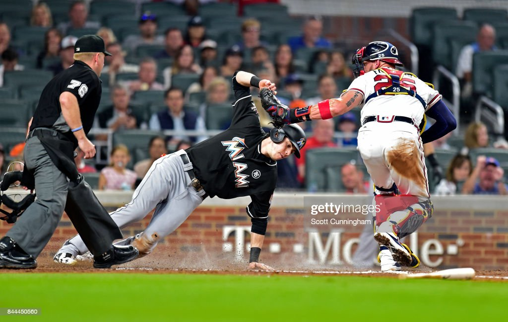 Christian Yelich #21 of the Miami Marlins is tagged out during the third inning at home by Tyler Flowers #25 of the Atlanta Braves at SunTrust Park on September 8, 2017 in Atlanta, Georgia.