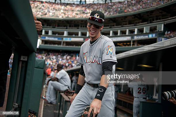 Christian Yelich of the Miami Marlins laughs before running onto the field to play defense in the ninth inning of a game against the Colorado Rockies...