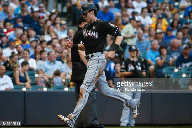 Christian Yelich of the Miami Marlins scores on a sacrifice fly by Justin Bour during the first inning at Miller Park on September 16 2017 in...