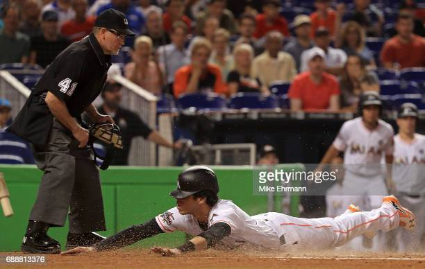Christian Yelich of the Miami Marlins slides into home to score a run past the tag from Martin Maldonado of the Los Angeles Angels in the first...