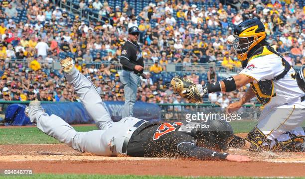 Christian Yelich of the Miami Marlins slides safely past Elias Diaz of the Pittsburgh Pirates to score on an RBI double by Marcell Ozuna in the first...