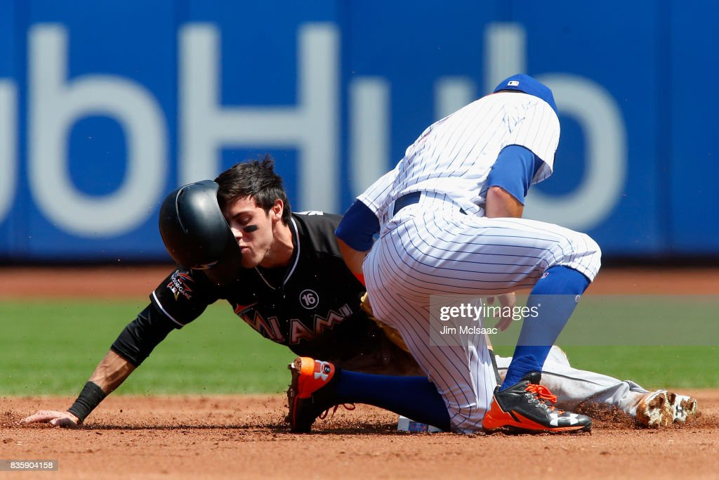 Christian Yelich #21 of the Miami Marlins steals second base in the first inning ahead of the tag from Gavin Cecchini #2 of the New York Mets at Citi Field on August 20, 2017 in the Flushing neighborhood of the Queens borough of New York City.