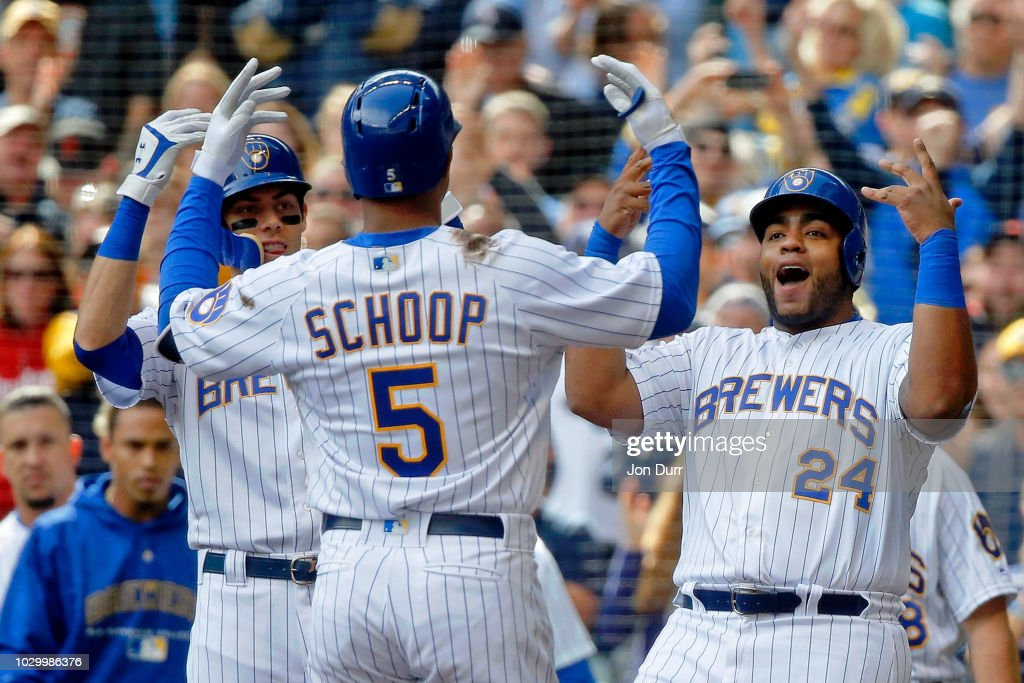 Christian Yelich #22 of the Milwaukee Brewers (L) and Jesus Aguilar #24 (R) celebrate the grand slam of Jonathan Schoop #5 against the San Francisco Giants during the sixth inning at Miller Park on September 9, 2018 in Milwaukee, Wisconsin.