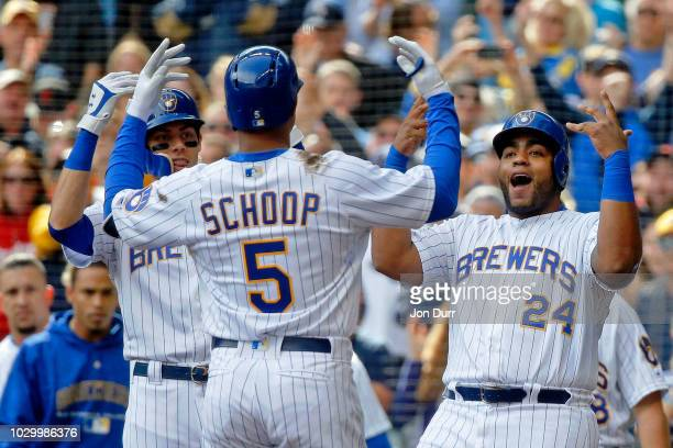 Christian Yelich of the Milwaukee Brewers and Jesus Aguilar celebrate the grand slam of Jonathan Schoop against the San Francisco Giants during the...