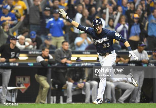 Christian Yelich of the Milwaukee Brewers celebrates as he runs home to score and win the game after teammate Mike Moustakas hits a walk off single...