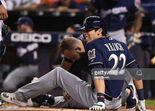 Christian Yelich of the Milwaukee Brewers is checked out by the medical staff after an injury from ball deflection in the first inning against the...