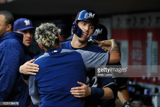 Christian Yelich of the Milwaukee Brewers is congratulated by a teammate after scoring in the first inning against the Cincinnati Reds at Great...