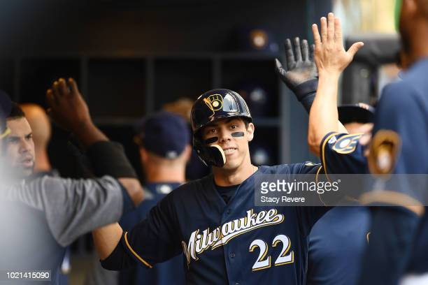 Christian Yelich of the Milwaukee Brewers is congratulated by teammates following a home run against the Cincinnati Reds during the first inning of a...